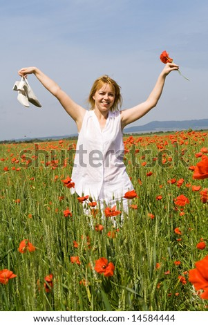Woman walking among poppies holding her shoes