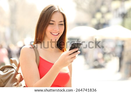 Woman walking and using a smart phone in the street in a sunny summer day - stock photo