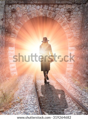 woman walking at the entrance of a tunnel