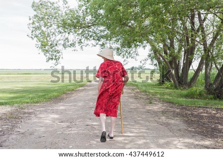 woman walking away with a cane - stock photo