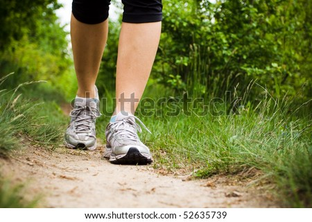 Woman walking cross country and trail in spring forest - stock photo