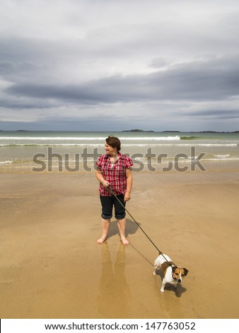 woman walking dog along beach of portrush east strand she has a jack russell terrier - stock photo