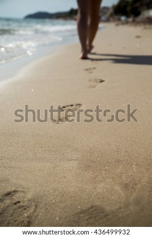 Woman walking down the beach, leaving footprints in the pebbles - stock photo