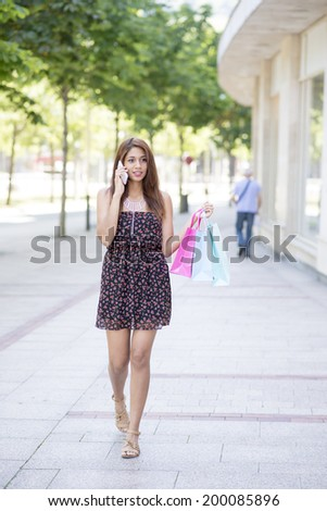 Woman walking down the street and talking on the phone.