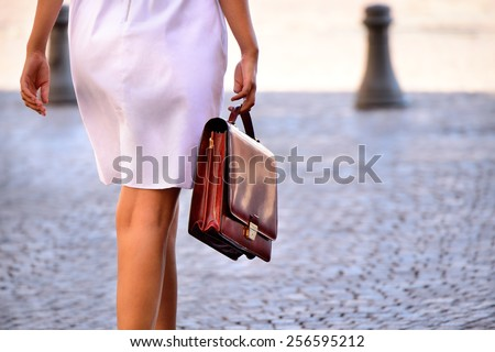 Woman walking home after work with portfolio bag - stock photo