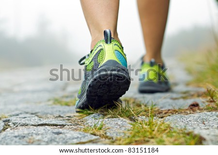 Woman walking in mountains in sport hiking shoes. Jogging or training outside in summer nature, motivational health and fitness concept.