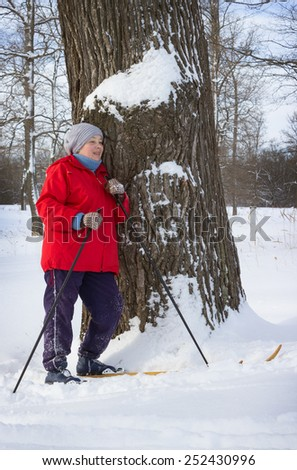 Woman walking in winter forest, tired and leaning against a tree. February