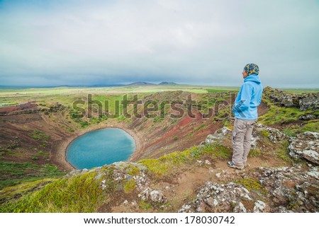 Woman walking near crater of a old active volcano Kerith filled with water. Iceland. - stock photo