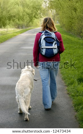 woman walking on a road with her dog