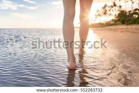 Woman walking on a tropical beach at sunset.