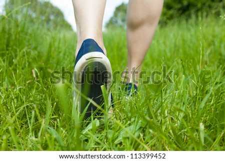 Woman walking on green grass in sport shoes - stock photo