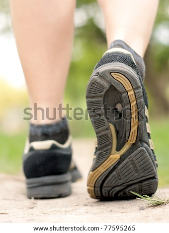 Woman walking on hiking trail in forest, sport shoe closeup - stock photo