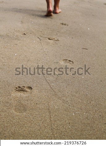 woman walking on sand beach leaving footprints in the sand - stock photo