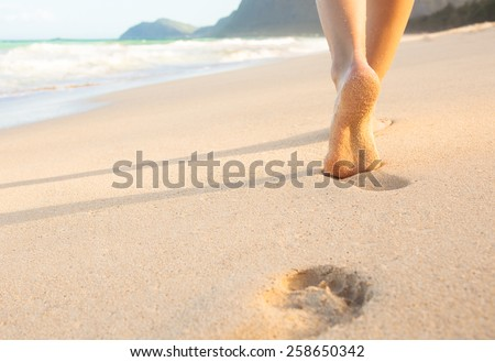 Woman walking on sand beach leaving footprints in the sand. - stock photo