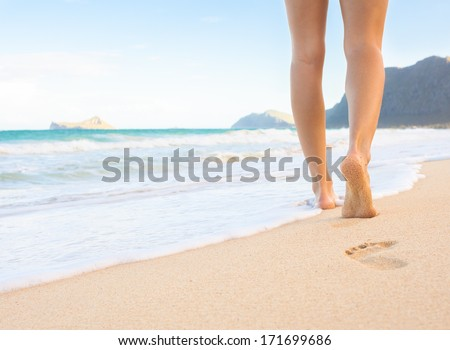 Woman walking on sand beach leaving footprints in the sand. Beach travel.  - stock photo