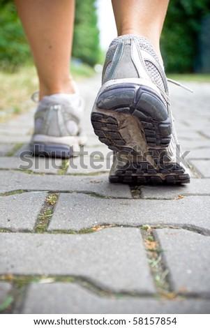 Woman walking on sidewalk, sport shoe close-up - stock photo