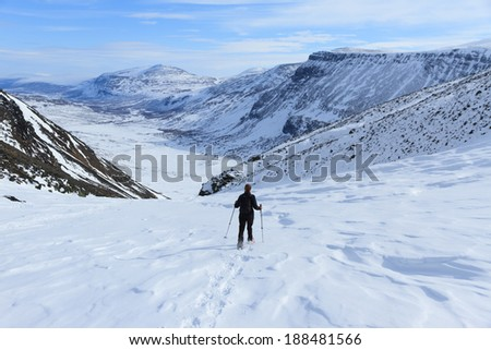 Woman walking on snowshoes near Kebnekaise mountain station in Swedish Lapland.