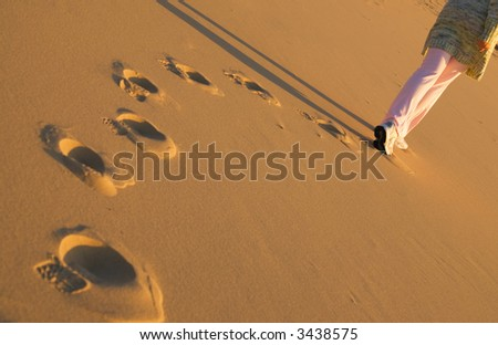 Woman walking on the beach at sunset time - stock photo