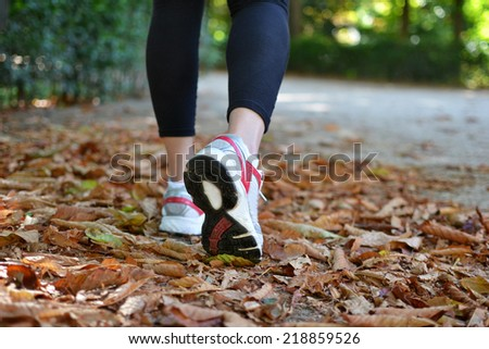 Woman walking on the fallen leaves of autumn - stock photo