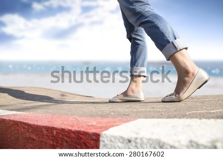 woman walking on the road and beach side background - stock photo