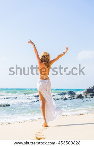 woman walking on the sand beach - stock photo