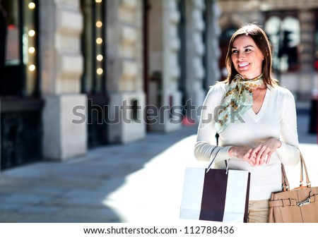 Woman walking on the street window shopping - stock photo