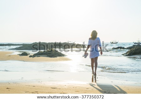 Woman walking on the tropical beach at sunset