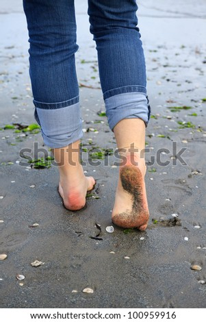 woman walking on the wet sand - stock photo