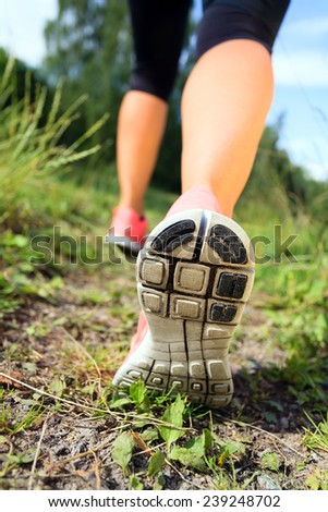 Woman walking or running exercise motivation and inspiration activity, legs on footpath green grass in forest, achievement fitness adventure and exercising in spring or summer nature healthy lifestyle - stock photo