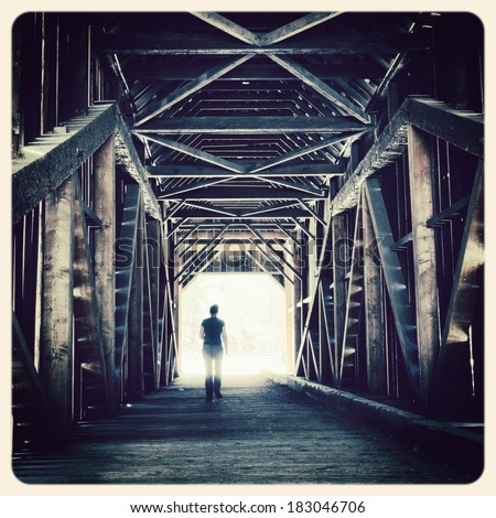 Woman walking towards the sunlight from a covered bridge. Filtered to look like an aged instant photo. - stock photo