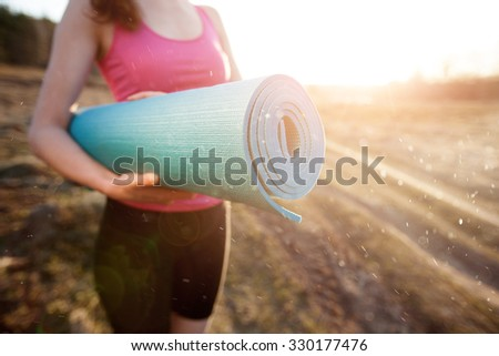woman walking with a yoga mat outside during sunset n a rural area wearing sports wear and doing yoga - stock photo