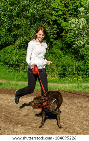 Woman walking with an American Stafford in the park - stock photo