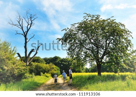woman wandering with two boys (her children) on a path near the forest