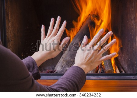 woman warming hands at fireplace - stock photo