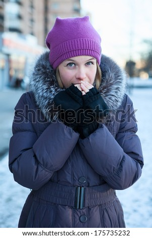 Woman warming hands at the cold winter weather - stock photo