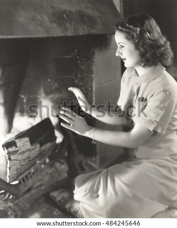 Woman warming her hands by the fireplace