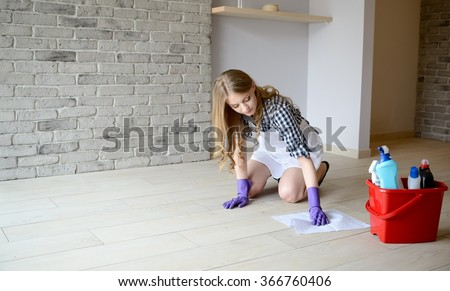 Woman washes the floor in the room on her knees. Dressed in a white apron and a plaid shirt. Protective rubber gloves on her hands - stock photo