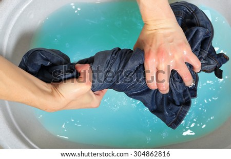 woman washing a pair of jeans by hand in plastic tub - stock photo