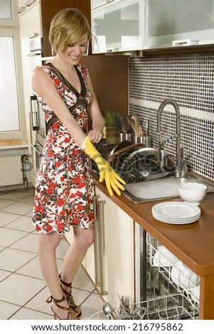 Woman washing dishes. - stock photo