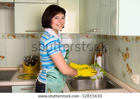 Woman washing dishes in kitchen.  Happiness girl in the apron washes a plate. - stock photo