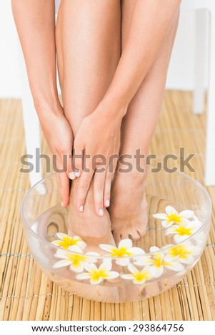 woman washing her feet in a bowl of flower at the spa institute