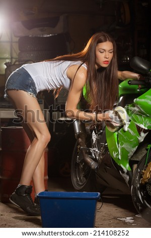 Woman washing motorcycle and preparing it for a ride