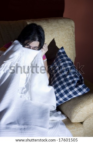 woman watching a scary and horror movie in the tv in a room - stock photo