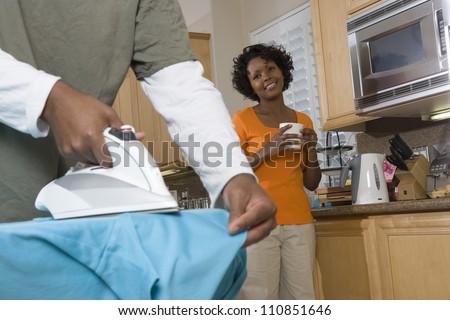 Woman Watching How Man Ironing His Shirt - stock photo
