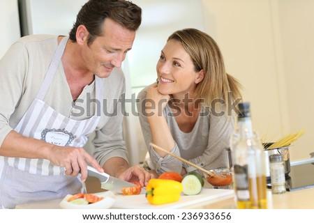 Woman watching husband preparing pasta dish - stock photo