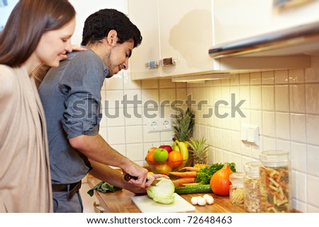 Woman watching man preparing vegetables in the kitchen - stock photo