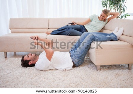 Woman watching television while her boyfriend is using his cellphone in their living room - stock photo