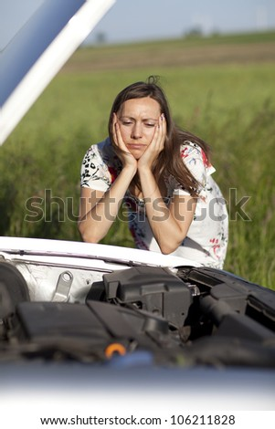 Woman watching the engine of a broken car
