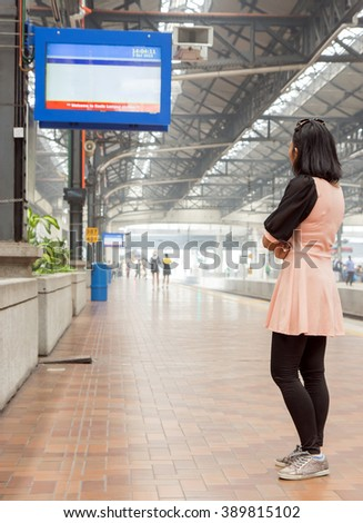 Woman watching the information board on the platform at the train station - stock photo