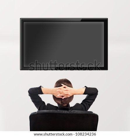 Woman watching tv. Photo from behind. Editable copyspace at the screen - stock photo